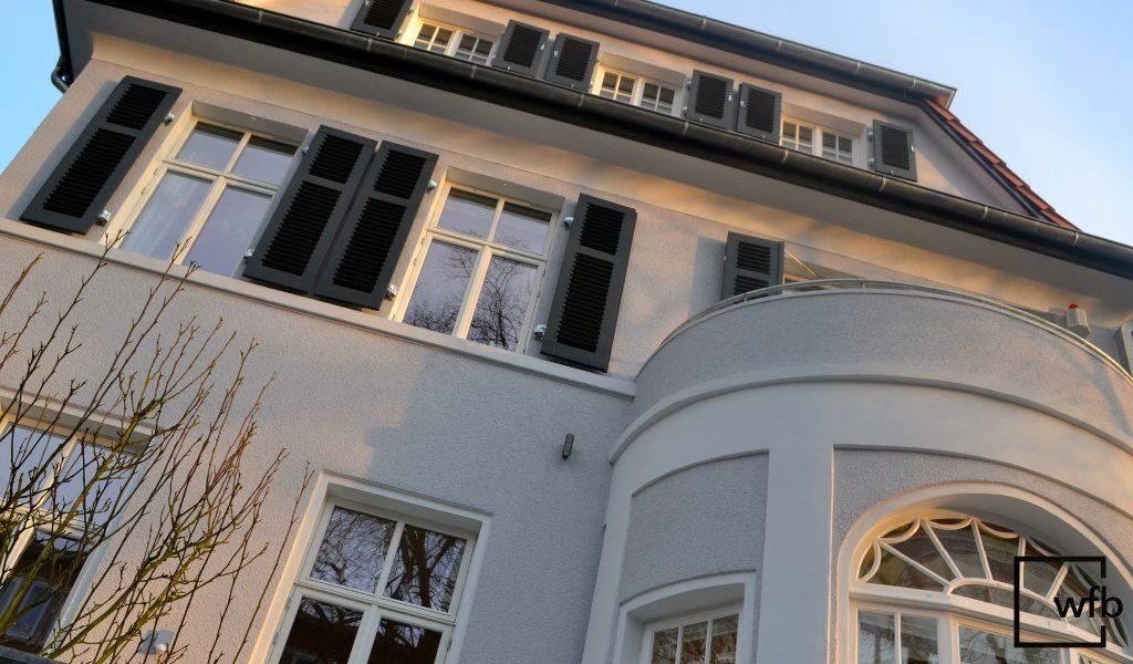 schlichte und hochwertige weiße Holzfenster von wfb mit Holzfensterläden in einer Stadtvilla